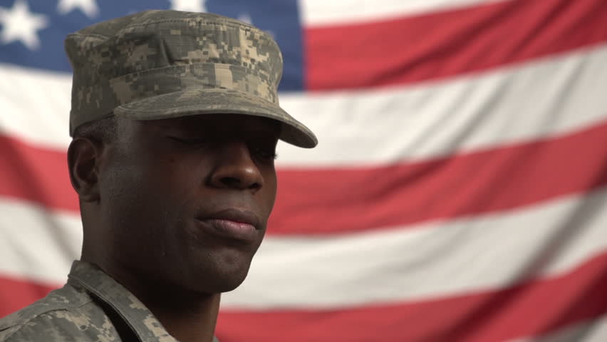 African American Male soldier, looking up in front of US flag
