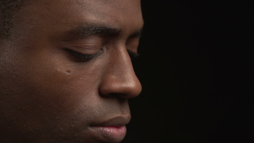 Close up African American man looking up, black background