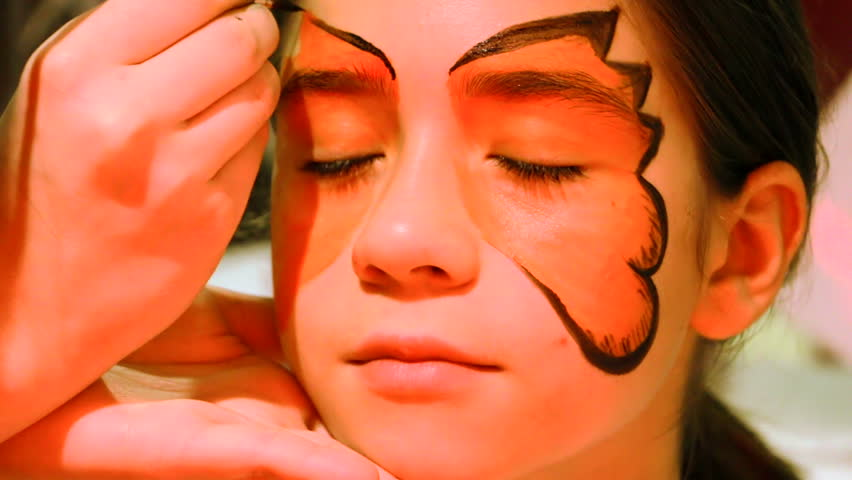 MONTENEGRO - PODGORICA, FEBRUARY 18, 2016 - Face painting. Woman artist painting face of little girl. Little girl getting her face painted