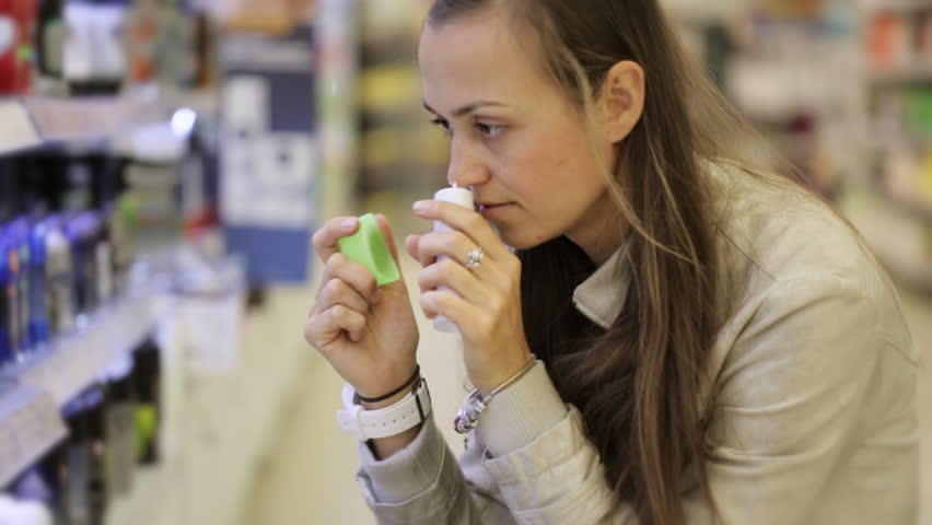 Young caucasian woman choosing deodorant in beauty section of shoping centre. No visible logos and trademarks.