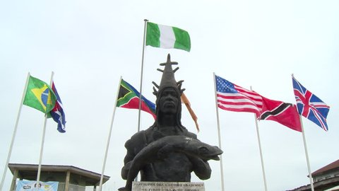 Osogbo, Nigeria - August 2013;Statue of Oba Larooye Gbadewolu, the first Ataoja of Osogbo, with flags of many nations behind.