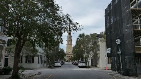 CHARLESTON, SOUTH CAROLINA  / UNITED STATES - OCTOBER 3, 2016: Cinematic shot of church steeple as camera tracks on street toward end of street where historic spire silhouettes beautiful cloudy sky.