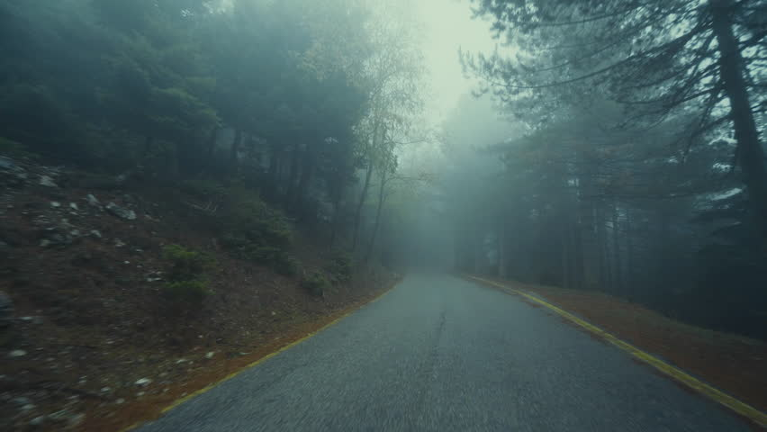 Pov driving on foggy dark scary mountain road at winter. Stabilized gimbal pov wide angle driving plate shot