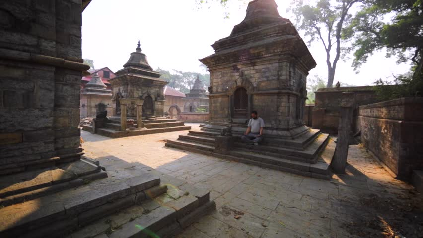 KATHMANDU, NEPAL - APRIL 11, 2016: The Pashupatinath Temple with small Shiva temples with lingams. Man does breathing exercises sitting on temple stairs.