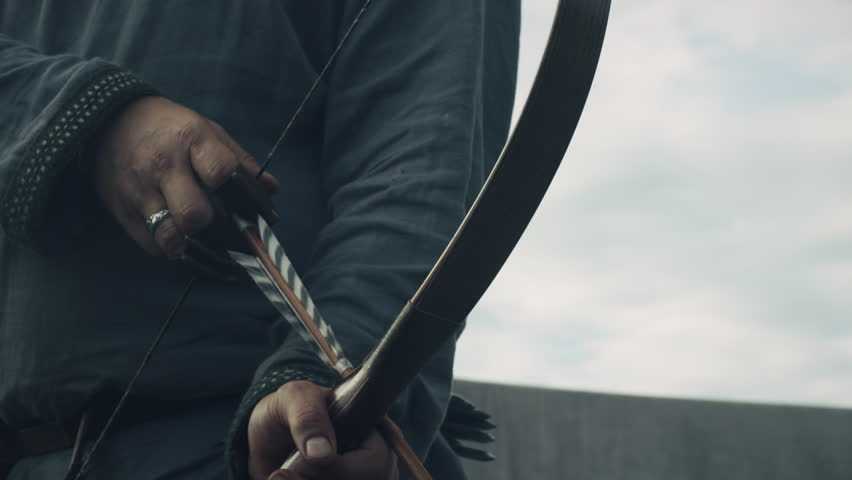 Medieval Archer Draws a Bowstring, Aims and Prepares to Shot. Medieval Reenactment. Shot on RED Cinema Camera in 4K (UHD).