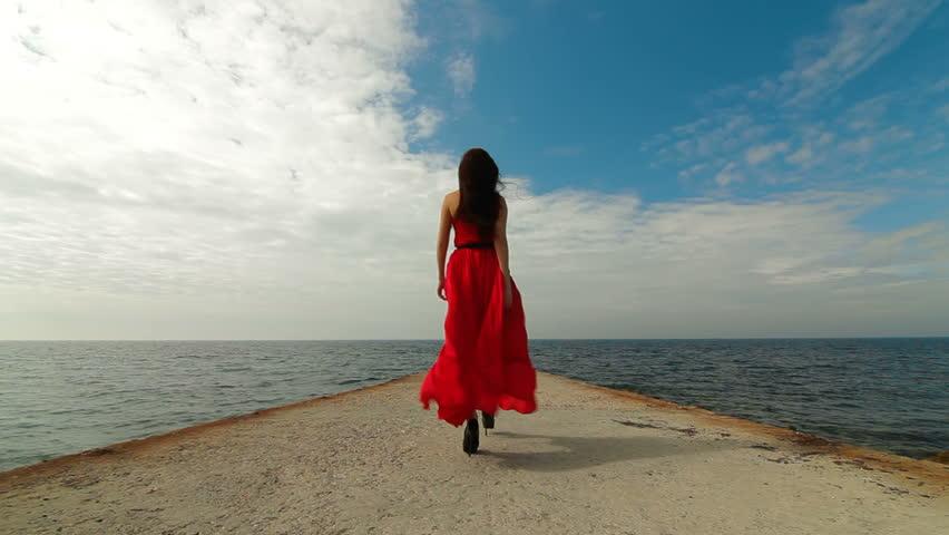 beautiful woman walking down pier in long red dress