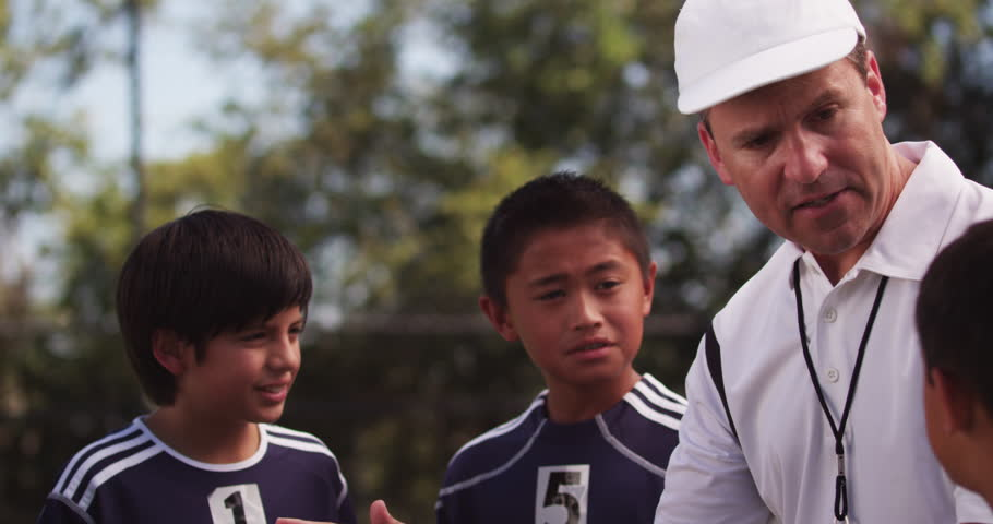 An enthusiastic coach gives his diverse team of youth league players a pep talk before sending them out onto the field. Version 3.