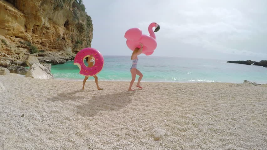 Beautiful girl Friends with inflatable flamingo donut on paradise beach vacation having fun on summer travel vacation | Shutterstock HD Video #21028039