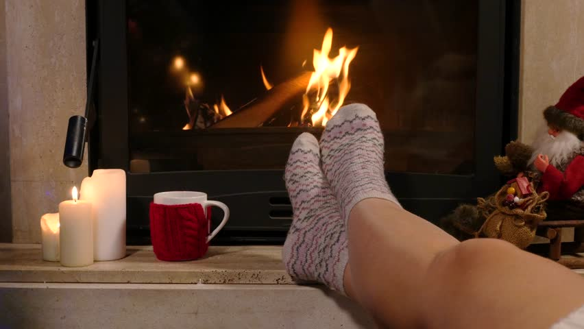 Woman Is Sitting With Cup Of Hot Drink And Book Near The Fireplace ...