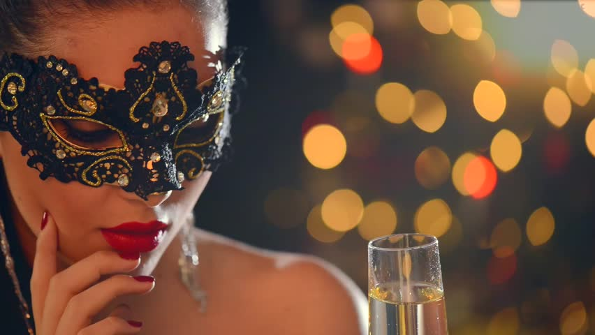 Sexy model woman with glass of champagne wearing venetian masquerade mask at party, drinking champagne over holiday glowing background. Christmas and New Year celebration. Full HD 1080p video footage