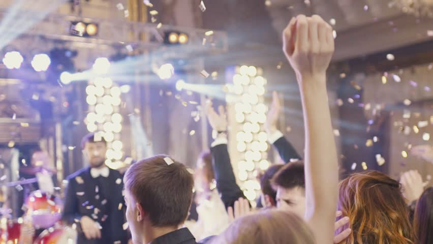 Delicate female hands cheering in the air the musical band in golden confetti. Club settings. Crowd of dancing people around. The singer applauses from the stage. Concert atmosphere.