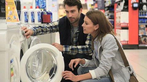 Seller helping customer with choosing washing machine