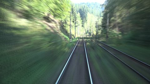 Timelapse of high speed train passing fast through the mountains and green forest