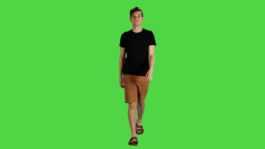Young man in a full shot walking towards the camera over a green screen. Casual look, Smiling, average speed, looking into the lens.