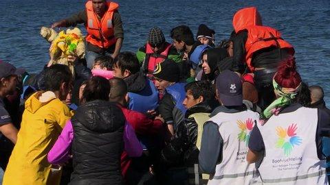 LESVOS, GREECE - NOV 2, 2015: Refugees leave rubber dinghy near the shore.