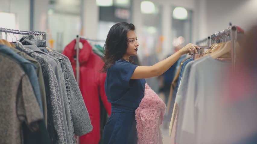 Shopping girl. Portrait of a beautiful woman in the store. Portrait of a young brunette girl with red lips in a clothing store. She chose a dress for a fitting. Fashionable brunette in stylish clothes | Shutterstock HD Video #21084733