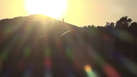 Boy on horse swinging lasso in sunset slow motion