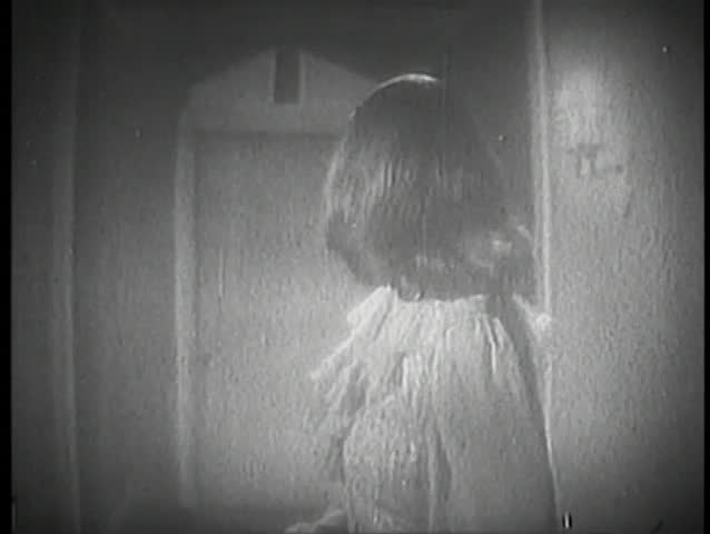 Rear view of woman in corridor looking at door in the distance