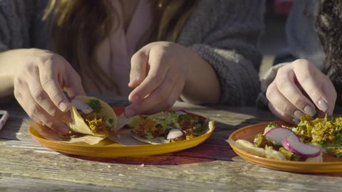 Closeup Of Woman Taking First Bite Of Her Taco, She Savors It