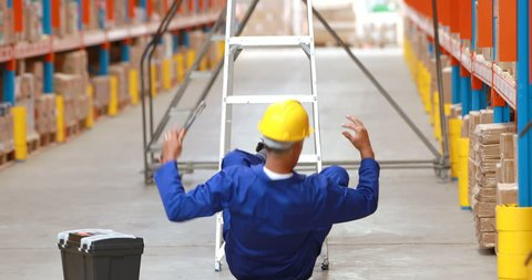 Front view of a Caucasian male warehouse worker falling off ladder while working in warehouse
