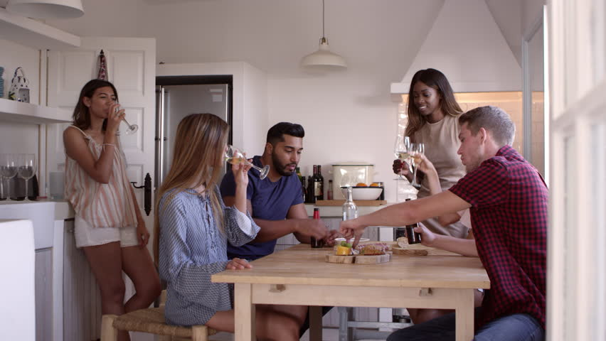 Young adult friends drinking and eating snacks in kitchen, shot on R3D