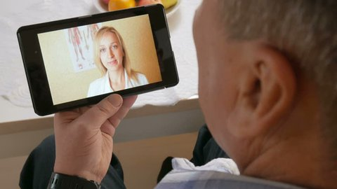 Aged man with a mustache in coughs and communicate with a doctor on a video conference. Doctor on a tablet online makes recommendations to the patient at home