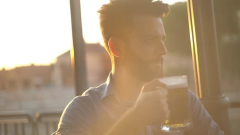 Close up shot of a young Caucasian man drinking beer outside at sunset time. Shot against the setting sun.