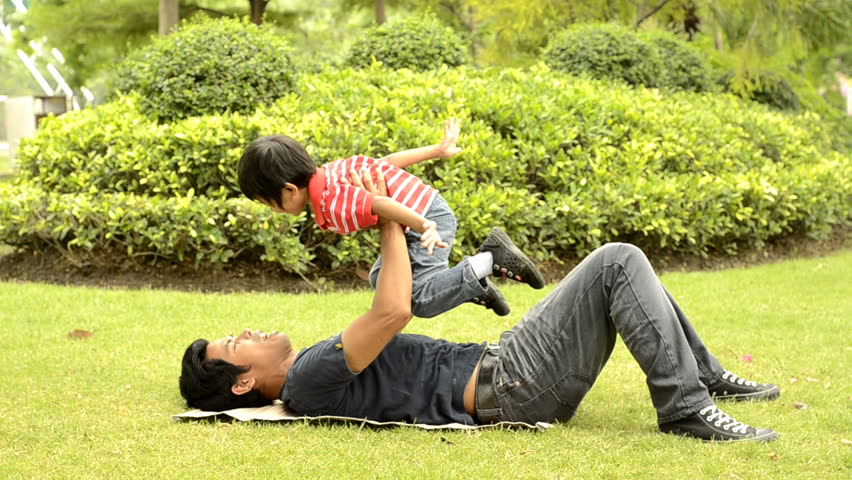 Asian father and son playing together on the grass in a park.