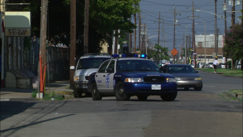 Day blue white police car emergency lights flashing towards day low income ghetto residential street with blue white police car out from behind 2 story aloadofball Images