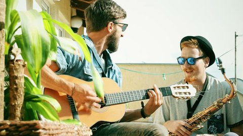 Handsome guy playing guitar while his friend with saxophone swaying to the beat, graded