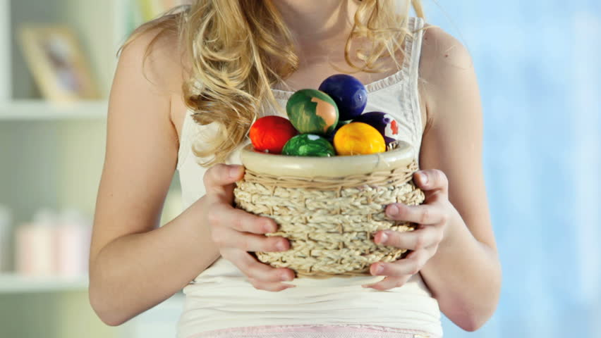 Pretty blond girl holding a basket full of colorful Easter eggs and smiling, camera moving bottom-upwards then down again