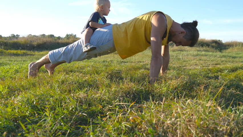 Young muscular father doing push ups with his little son on his back. Athletic man doing push-ups at green grass with happy smiling baby sitting on his rear. Strong guy spending time with your child #21207259