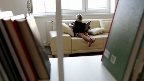 A camera peeks in on a little boy reading a book from behind a book shelf