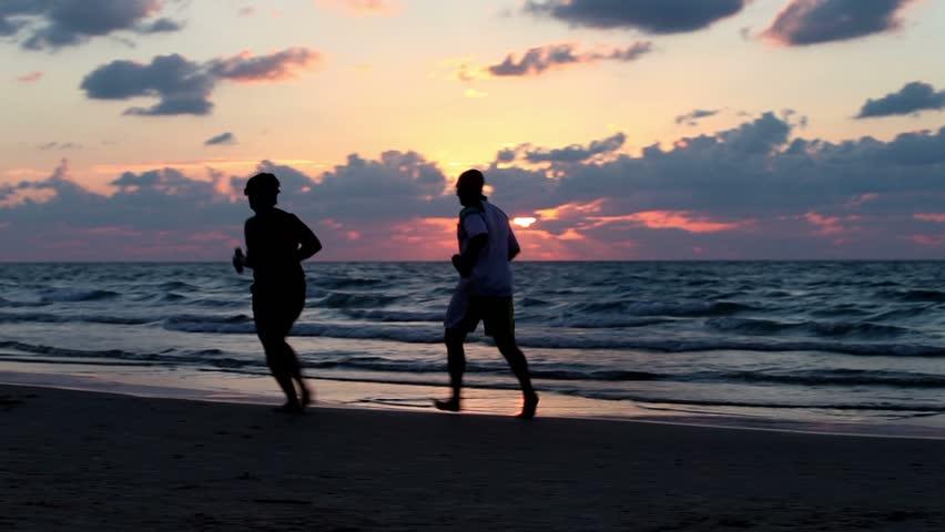 Tel - Aviv,  Israel – November 6, 2016: Silhouettes of men and women running along the seashore at sunset. #21243019