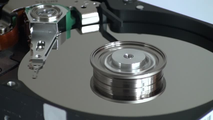 Metal circle plate and magnetic head inside hard disk drive reading and writing data   Shutterstock HD Video #21255607
