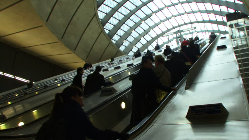 Low angle wide shot of commuters on escalators under glass canopy at Canary Wharf station, the London Underground