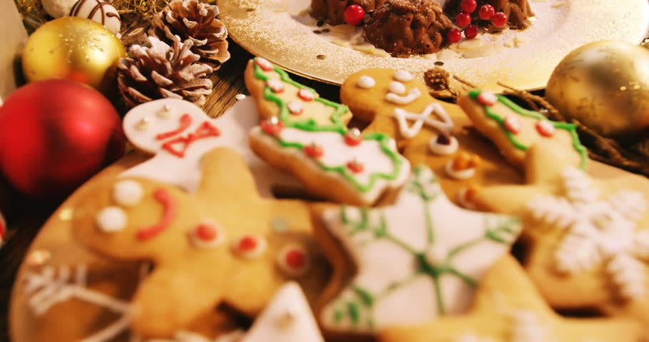 Close-up of various christmas desserts and gifts on wooden table 4k