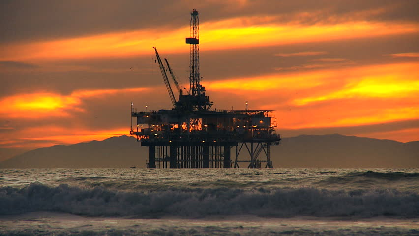 Fossil fuel pumping industrial oil rig at dusk