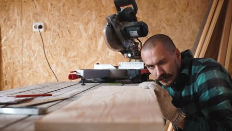 Focused bold carpenter with vintage moustache at work with wooden plank