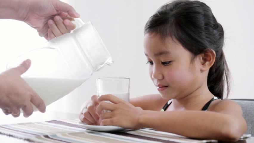 Young girl drinking fresh milk.