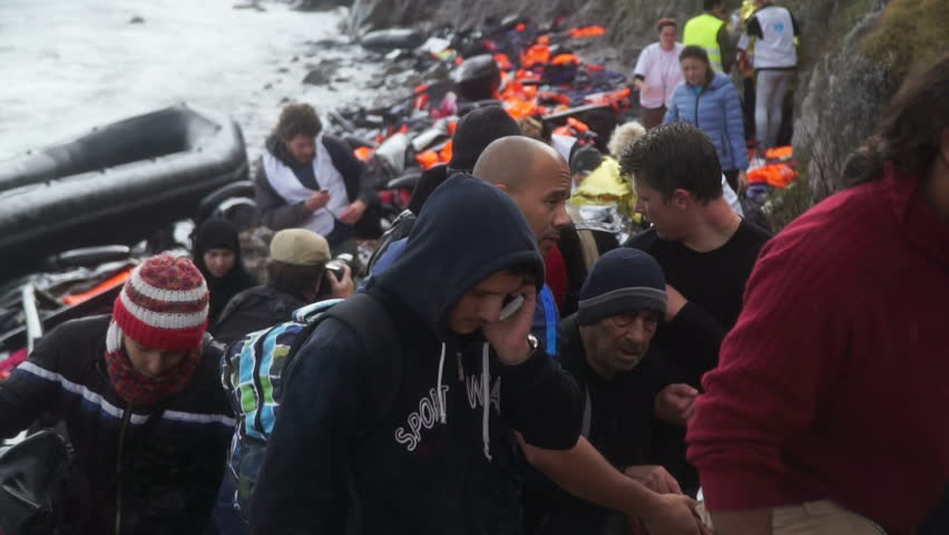 LESVOS, GREECE - NOV 5, 2015: Refugees leave rubber dinghy near the rocky shore.