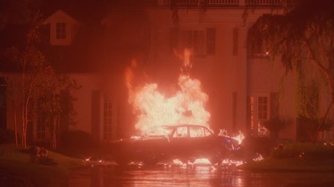 night Black car parked driveway front 2 story white mansion columns turrets Car explodes, blazing fire Man runs very end