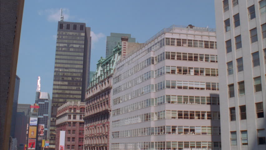city building side. day High angle Pan right over city buildings side Raked large modern  stone corner office Day Angle Right Over City Buildings Tight Side