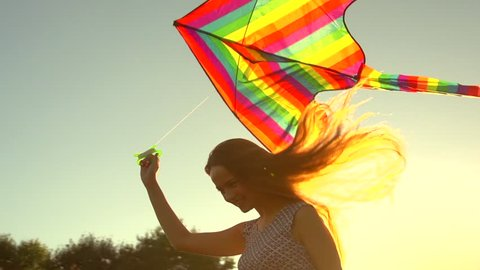 Beauty girl in short dress running with kite on the field. Beautiful young woman with flying colorful kite over clear blue sky. Free, freedom concept. Emotions, healthy lifestyle. Slow motion 240 fps