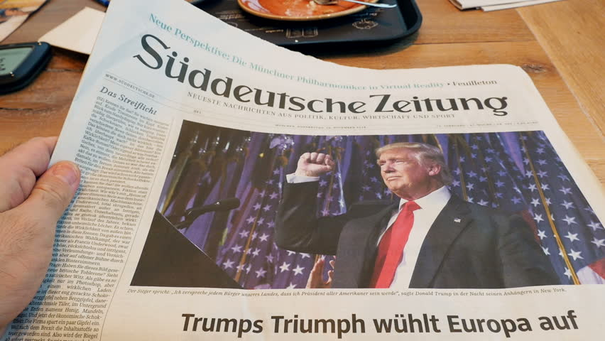 FRANKFURT, GERMANY - NOV 10, 2016: POV of Man reading in German Caf\xE9 about the Suddeutsche Zeitung newspaper with Donald Trump elected as President as the 45th President of United States of America