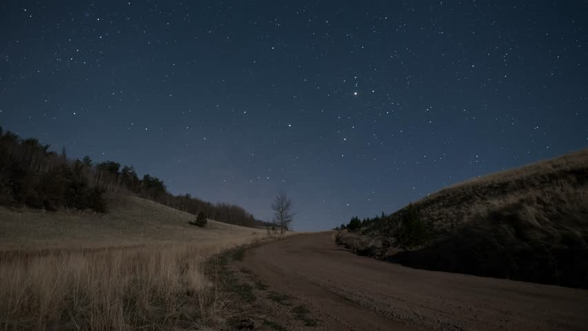 Milky Way night sky timelapse with dirt road and shadows