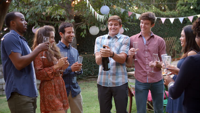 Friends Celebrating With Champagne At Outdoor Backyard Party