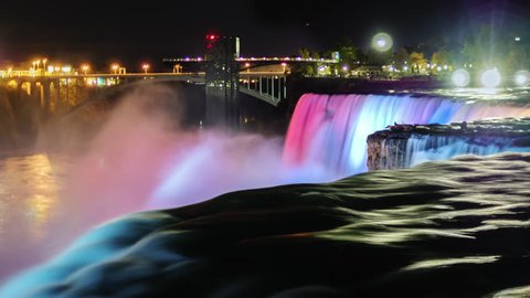 Niagara Falls at night. The jets of falling water are illuminated with colored spotlights. The flow of water on a dark foreground