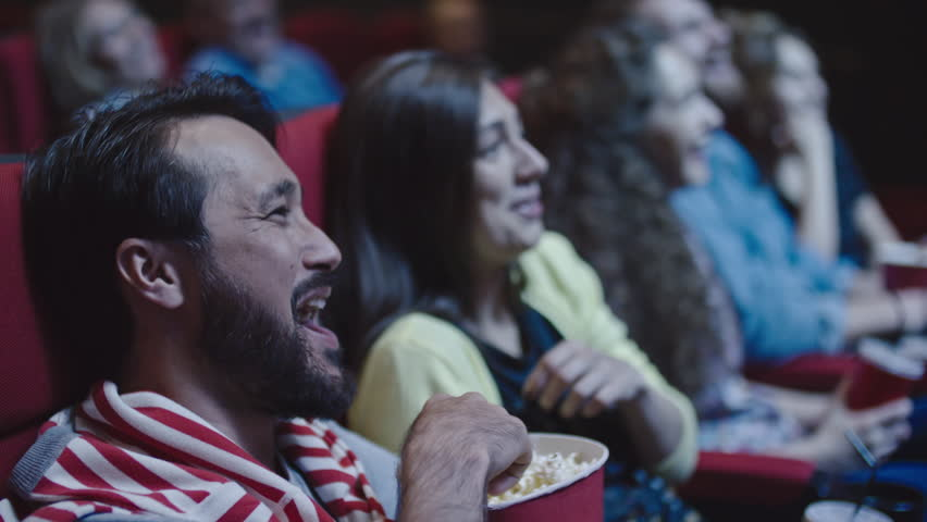 Closeup of young couple sharing popcorn while watching comedy in movie theater | Shutterstock HD Video #21420541