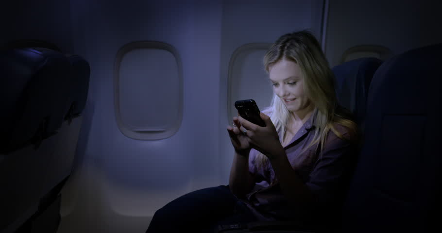 Attractive young woman using a cellphone on airliner at night. Medium long shot from side angle,  recorded hand-held at 60fps